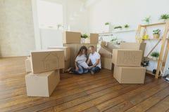 Dobiera się planować ich nowego żywego pokój jest usytuowanym na podłoga młody rodzinny chodzenie nowy mieszkanie i przewożeń pud Fotografia Royalty Free