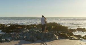 Dobiera się pozycję na skalistym brzeg przy plażą 4k zbiory wideo