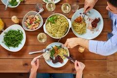 Dobiera się przy stołem z karmowym łasowanie makaronem, kurczakiem i Zdjęcia Royalty Free