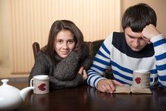 Dobiera się przy stołowym pije czytaniem i herbatą książka Obrazy Stock