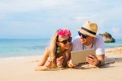 Dobiera się relaksować na plaży i patrzeć pastylka komputer obraz stock