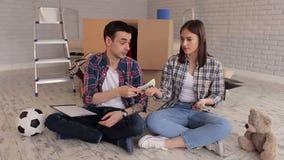 Dobiera się siedzi na podłoga w ich nowym mieszkaniu wśród pudełek i liczy pieniądze zdjęcie wideo