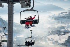 Dobiera się snowboarders ma zabawę na narciarskim dźwignięciu w ośrodku narciarskim z pięknym tłem śnieżyści skłony, wzgórza obraz royalty free