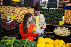 Dobiera się sprawdzać ich notepad podczas gdy robiący zakupy w organicznie sekci zdjęcie stock