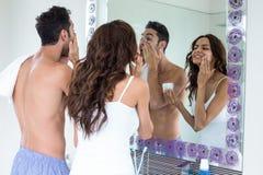 Dobiera się stosować śmietankę na twarzy podczas gdy patrzejący w lustrze Zdjęcie Stock