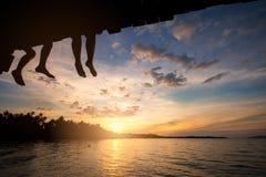 Dobiera się sylwetki i dopatrywania słońce przy zmierzchem na plaży w Tajlandia Obraz Royalty Free