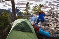 Dobiera się turystów kobieta i mężczyzna obsiadania przy obozem w lesie i fotografia stock