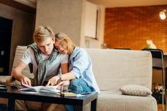 Dobiera się uczni studiuje, czytelnicza książka podczas gdy siedzący na kanapie zdjęcie royalty free