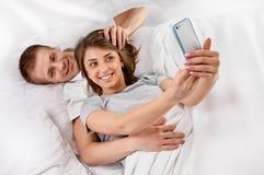 Dobiera się w łóżku bierze obrazek z smartphone Zdjęcie Royalty Free
