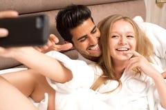 Dobiera się w łóżku bierze selfie i ma zabawę, para w łóżku bierze obrazek z smartphone Obraz Royalty Free