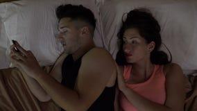 Dobiera się w łóżku przy nocą uzależniającą się smartphone na internetów ogólnospołecznych środkach ignoruje jego żony zdjęcie wideo