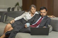 Dobiera się w domu w formalware z mężczyzna działaniem i kobiety dopatrywaniem Zdjęcie Stock