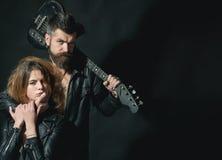 Dobiera się w miłości cuddling z gitarą, czarny tło Rock and roll pojęcie Gitarzysta z brodą i seksowna dziewczyna w staniku Obrazy Royalty Free