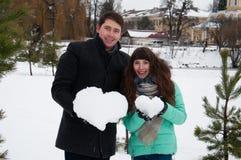 Dobiera się w miłości dziewczyny i faceta mienia sercach od śniegu zdjęcia stock