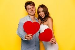 Dobiera się w miłości pozuje przy kamerą, trzyma czerwonych serca Obraz Stock