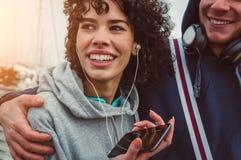 Dobiera się w miłości słuchającej muzyce od hełmofonów używać smartphone obraz stock