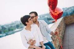 Dobiera się w miłości trzyma czerwonych baloons serca na walentynki Obrazy Royalty Free