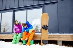 Dobiera się w narciarskich kostiumach blisko nowożytnego domu w górach zdjęcie stock