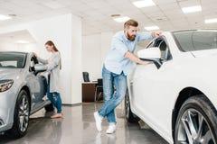 Dobiera się wybierać samochód, mężczyzna i kobiety patrzeje na różnorodnych samochodach, obrazy royalty free