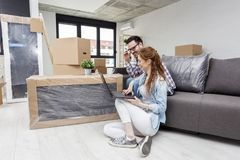 Dobiera się obsiadanie na kanapie w mieszkaniu z komputerem obraz stock