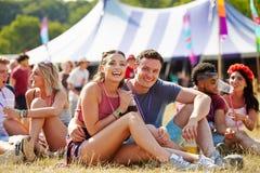 Dobiera się obsiadanie na trawie w widowni przy festiwalem muzyki Obraz Royalty Free