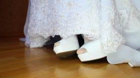 Dobladillo del vestido de boda de los puntos bajos de la novia y primer de los zapatos del blanco de las pieles