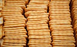 Doblado en las galletas cuadradas sabrosas de una caja Foto de archivo