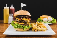 Doble burger with doble cheddar cheese, lettuce, bacon, mushrooms and french fries stock photos