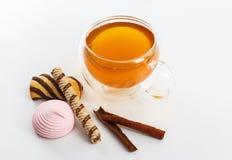 Doble la taza de cristal de la pared echada a un lado llena de té verde con los dulces y las galletas Foto de archivo