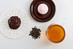 Doble la taza de cristal de la pared echada a un lado llena de té verde con los dulces y las galletas Fotografía de archivo