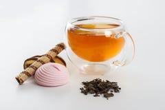 Doble la taza de cristal de la pared echada a un lado llena de té verde con los dulces y las galletas Fotografía de archivo libre de regalías