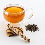 Doble la taza de cristal de la pared echada a un lado llena de té verde con los dulces y las galletas Fotos de archivo