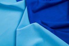 Dobleces del tejido triangular azul como fondo Imagenes de archivo