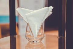 Doblez ordenado de la manera de la servilleta en el ajuste de cristal en la mesa de comedor para la cena en hotel de lujo fotos de archivo