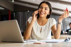 Dobra biznesowa rozmowa Rozochocona młoda piękna kobieta opowiada na telefonie komórkowym i używa laptop z uśmiechem przy podczas obrazy royalty free