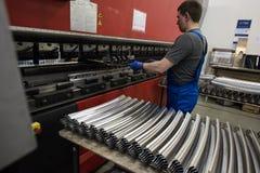 Dobra das placas de aço em uma máquina especial na planta do tra Imagens de Stock