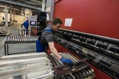 Dobra das placas de aço em uma máquina especial na planta do tra Foto de Stock