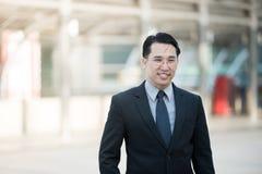 Dobra przyglądająca Azjatycka biznesowego mężczyzna pozycja z formalnym kostiumem Zdjęcie Stock