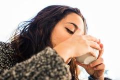 Dobra przyglądająca dziewczyna pije cappuccino - widok spod spodu fotografia royalty free
