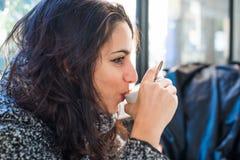 Dobra przyglądająca dziewczyna pije cappuccino - zamyka w górę widoku zdjęcie royalty free