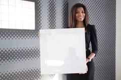 Dobra przyglądająca młoda biznesowa dama w czarnego silnego apartamentu chwyta pustym papierze Obrazy Royalty Free