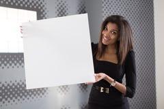 Dobra przyglądająca młoda biznesowa dama w czarnego silnego apartamentu chwyta pustym papierze Fotografia Royalty Free