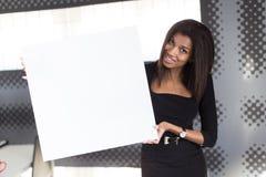 Dobra przyglądająca młoda biznesowa dama w czarnego silnego apartamentu chwyta pustym papierze Zdjęcie Royalty Free
