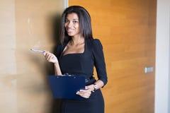 Dobra przyglądająca młoda biznesowa dama w czarnej silnej apartamentu chwyta pastylce Fotografia Royalty Free