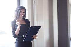 Dobra przyglądająca młoda biznesowa dama w czarnej silnej apartamentu chwyta pastylce Zdjęcie Stock