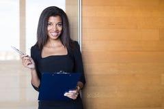 Dobra przyglądająca młoda biznesowa dama w czarnej silnej apartamentu chwyta pastylce Fotografia Stock