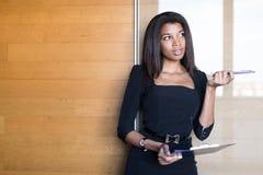 Dobra przyglądająca młoda biznesowa dama w czarnej silnej apartamentu chwyta pastylce Obraz Royalty Free
