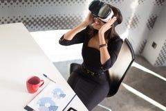 Dobra przyglądająca młoda biznesowa dama w czarnym silnym apartamencie siedzi przy biurowym stołem w vr szkłach Fotografia Stock
