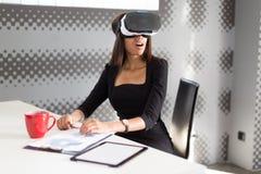 Dobra przyglądająca młoda biznesowa dama w czarnym silnym apartamencie siedzi przy biurowym stołem w vr szkłach Zdjęcie Stock