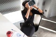 Dobra przyglądająca młoda biznesowa dama w czarnym silnym apartamencie siedzi przy biurowym stołem w vr szkłach Zdjęcia Stock